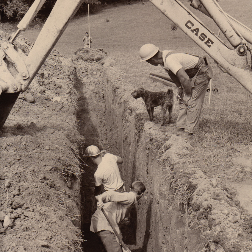 With the help of volunteer Bob Murphy, Larry & Randy Carlson dig one of the first trenches to run water and utilities to the buildings.
