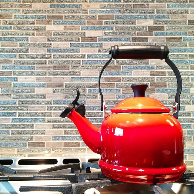 red le creuset teapot against blue and grey backsplash