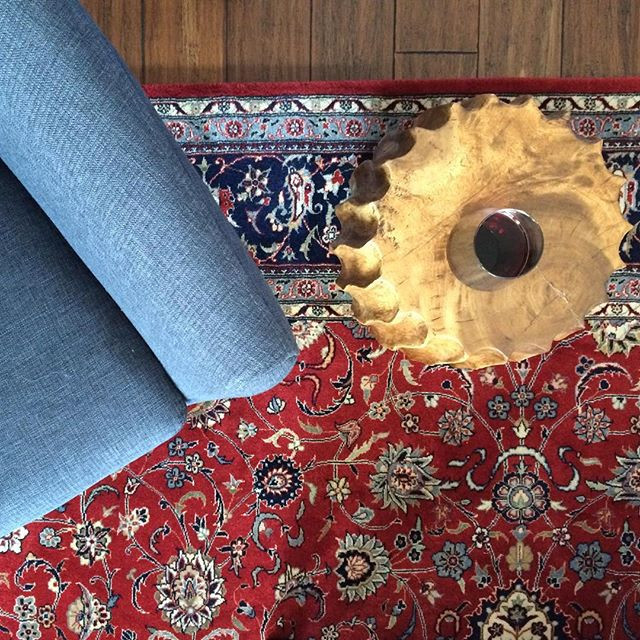 modern blue twill chair with traditional red and blue persian rug