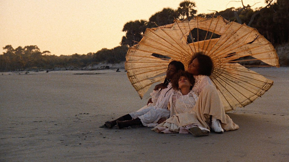 Daughters of the Dust, immagine del film di Julie Dash, tre donne Nere sotto un ombrello bianco