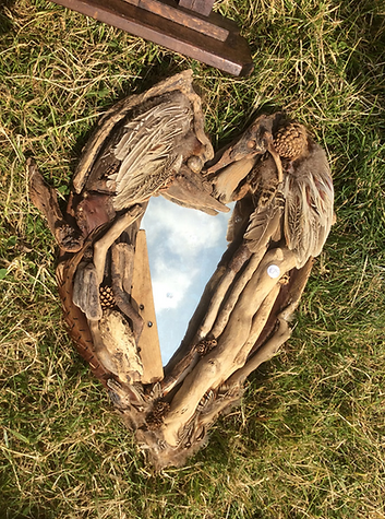 Natural wood mirror with fir cones and feathers.