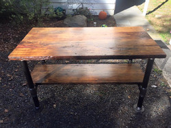 Reclaimed floorboards from a horse barn with  iron pipe base.