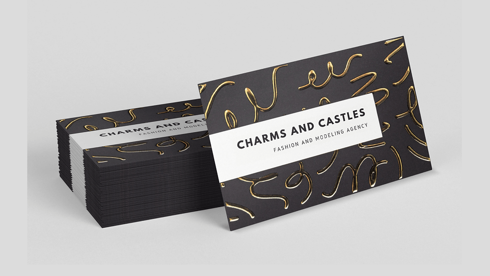 A stack of black business cards with gold foiling details.