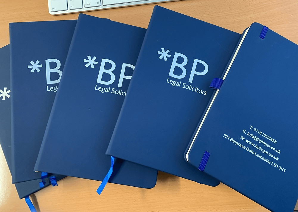 Blue promotional notebooks branded with a company logo.
