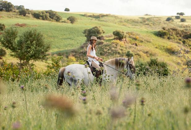 side-view-of-female-farmer-horseback-riding-outdoors.jpg