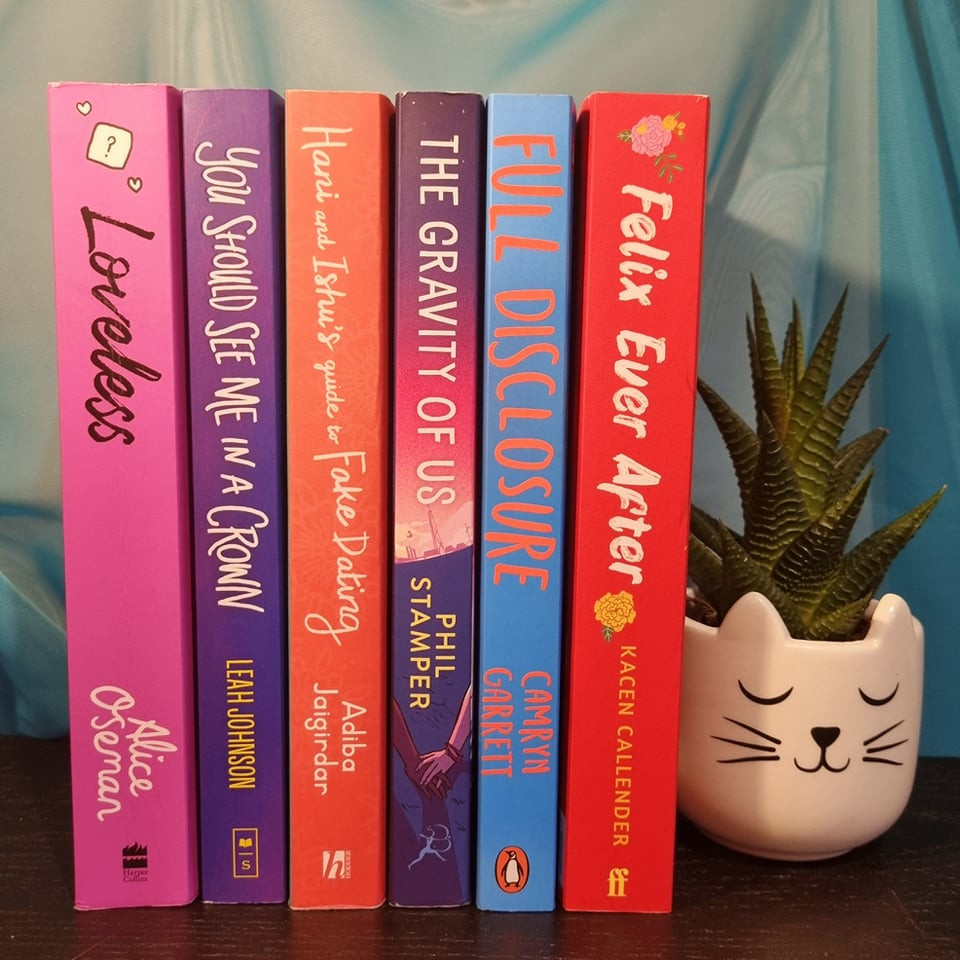 Stack of YA books with a small Aloe Vera plant in a cat shaped pot: Loveless, You Should See Me in a Crown, Hani and Ishu's Guide to Fake Dating, The Gravity of Us, Full Disclosure, Felix Ever After