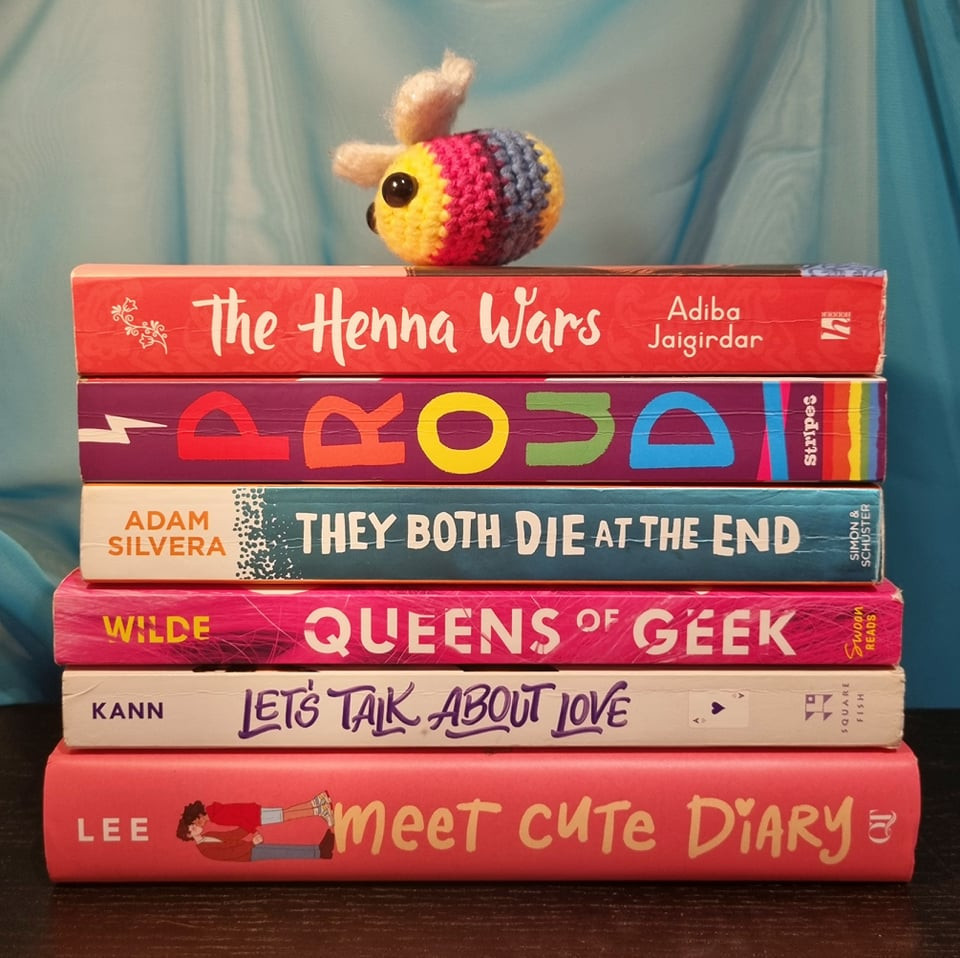 Stack of YA books with a small, crocheted bee in bi flag colours on top: The Henna Wars, PROUD, They Both Die in the End, Queens of Geek, Let's Talk About Love and Meet Cute Diary