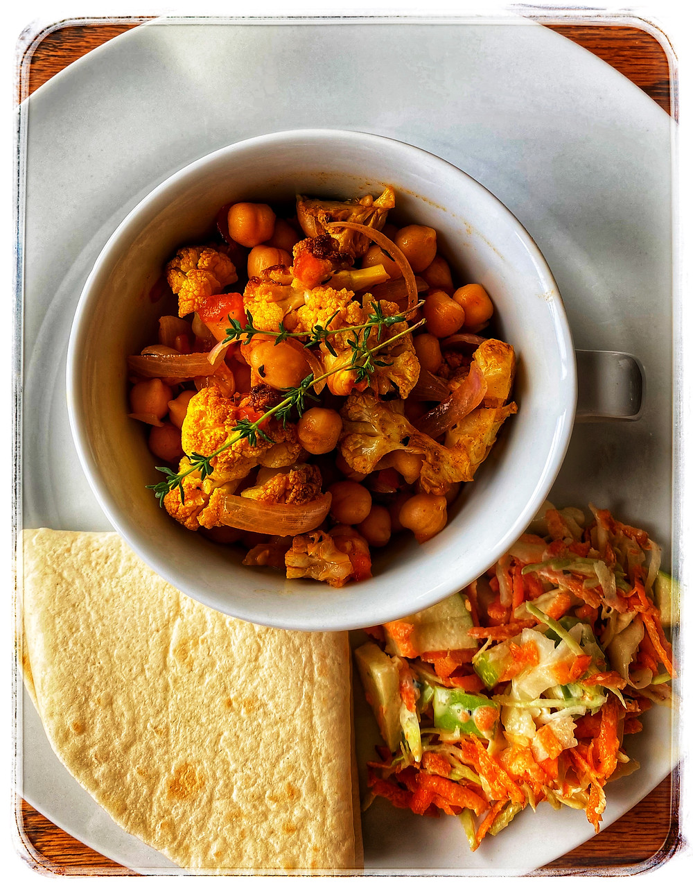 A meal of spicy baked Cauliflower with chickpea stew, Coleslaw and tortillas. Image credit: Nicole Cullinan @wellnessplaceint