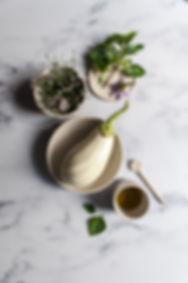 dark mood food photography, white eggplant, ceramics, basil, marble background