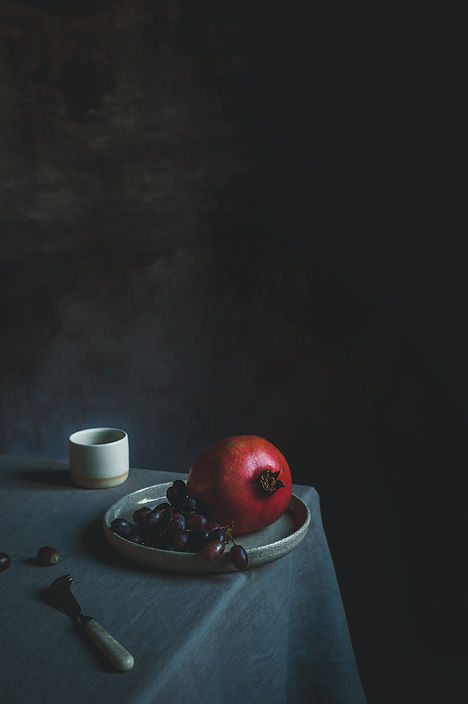 dark mood food photography, pomegranate, Vermeer light, minimalism, pomegranate