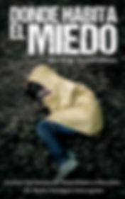 Portada de la novela Dond Habita el Miedo. Sobre un suelo de hojarasca, una chica con un impermeable amarillo, encogida en el suelo, de costado, tapándose la cara con las manos. Imagen distorsionada, transmite inseguridad y confusión.
