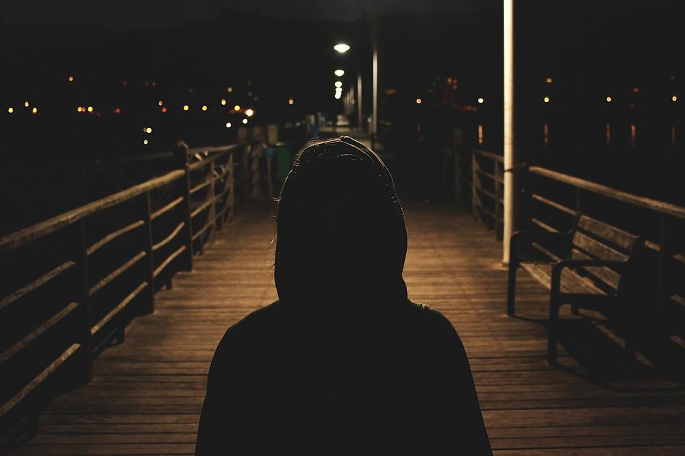 figura solitaria en un muelle oscuro