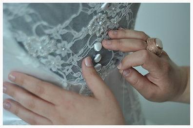 Robe de mariée avec dos nu, en dentelle blanche fleurie. Faux boutonnage et borderie de perles à la mains.