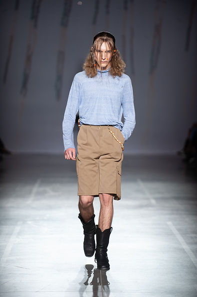 MASHAT SS20 Collection - UFW fashion show. Look 10: model dressed in sky blue turtleneck with light wooden beads chains and button details on the collar, soft jeans bermuda with patch pockets and wooden beads chain