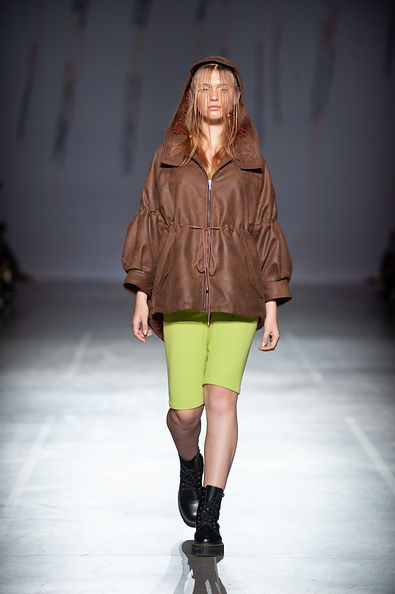 MASHAT SS20 Collection - UFW fashion show. Look 7: model dressed in light-green bicycles and mantle coat from faux textured leather with a hood