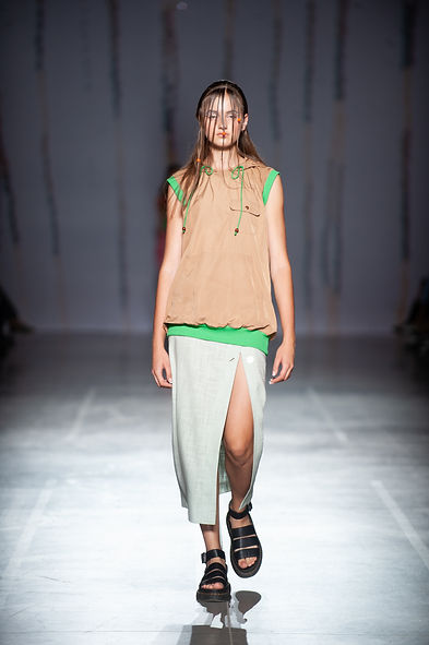 MASHAT SS20 Collection - UFW fashion show. Look 3: model dressed in unisex beige hoodie-vest with green grass elastic elements on the hem and on the armholes, mint maxi low cut skirt