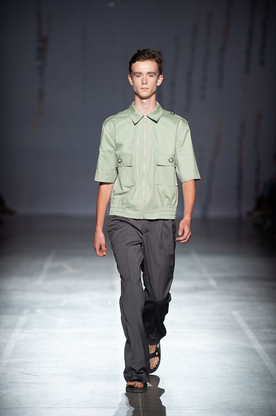 MASHAT SS20 Collection - UFW fashion show. Look 2: male model dressed in menthol jacket with short sleeves and unisex grey pleated pants with extended length