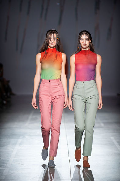 MASHAT SS20 Collection - UFW fashion show. Look 5.4: twin models dressed in cigarette jeans in coral and menthol colors and mesh turtleneck tops in pinky and green-orange tones