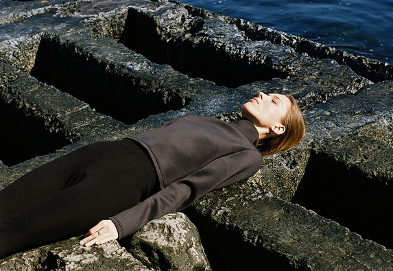 MASHAT AW18/19 Collection: girl lies on a post-apocalyptic background, wearing black leggins with scraps and black neoprene troyer
