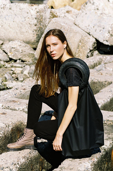 MASHAT AW18/19 Collection: girl sitting on concrete blocks, wearing black legging with scraps and holding shopper-bag with tire handles.