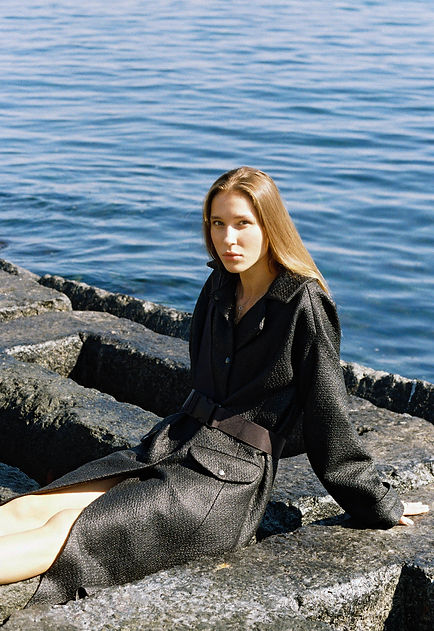 MASHAT AW18/19 Collection: girl sitting on concrete blocks, wearing black lackered coat with the safety belt. On the background - the Black sea