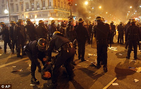 Police officers arrest a demonstrator after the protest march in downtown Paris