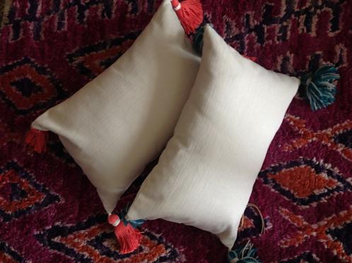 Textured cream linen throw pillow with merino wool tassels.
