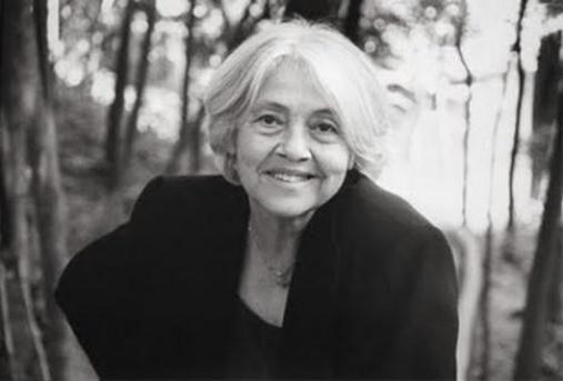 Foto da escritora Adélia Prado. Foto de Adélia em preto e branco frontal ao ar livre.