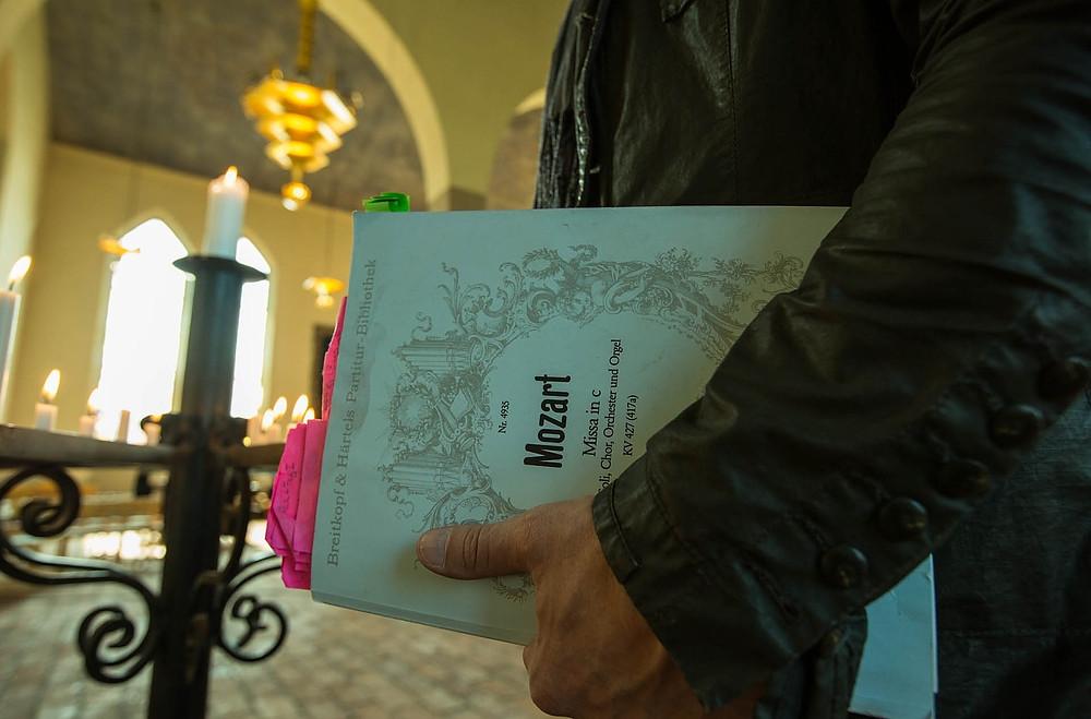 Mão de homem carregando partituras musicais. Na capa aparece escrito Mozart. Ambiente  de uma Igreja.