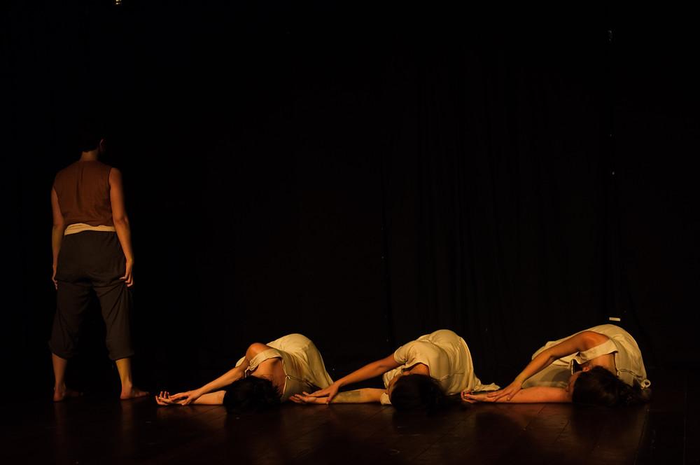 foto de espetáculo da Cia Corpoiesis, três bailarinas deitadas no chão e uma bailarina em pé de costas ao fundo do palco.