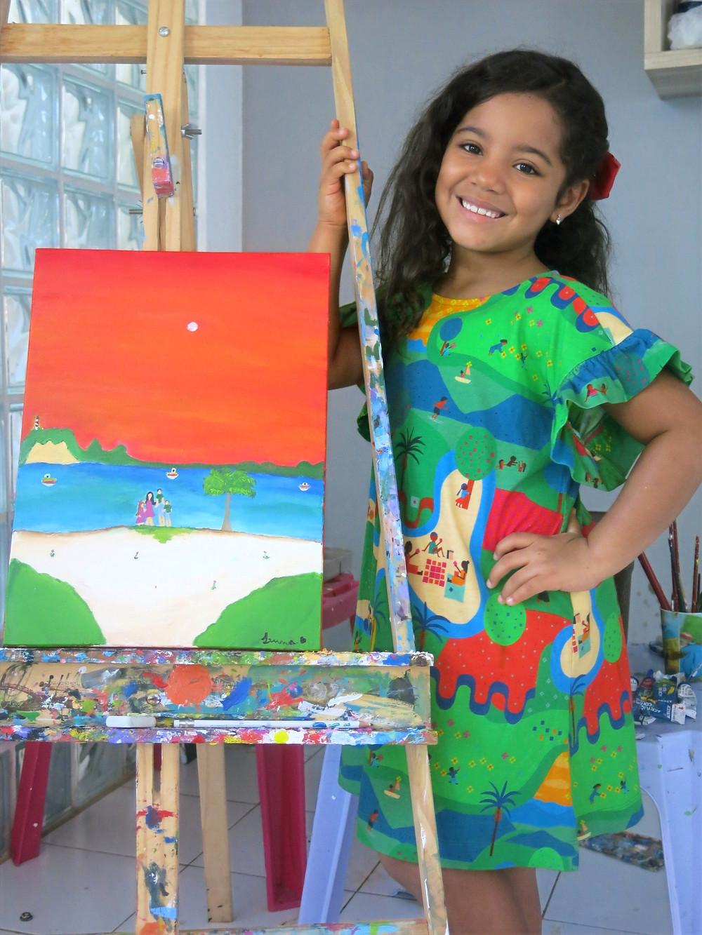A artista mirim Luna Belém pousa ao lado do cavalete com uma de suas telas. A tela retrata uma praia com céu alaranjado. Luna está de vestido estampado e sorrindo para a câmera.