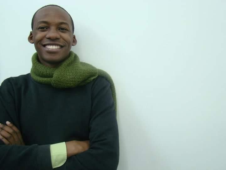Foto do artista plástico Pedro Ivo Cipriano. foto de frente, Cipriano sorri para a câmera, está vestindo blusa preta e cachecol verde. fundo branco.
