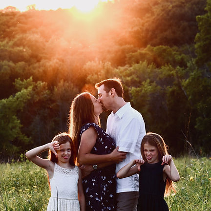 Husband and wife kissing and in love in forest with sunset behind them.  Daughters are making funny faces posed in front of them.  Family photoshoot in Waukesha, Wisconsin. Noelle Angelique Photographer