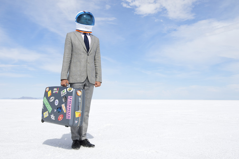 businessman wearing an astronaut helmet and holding a suitcase with many stickers