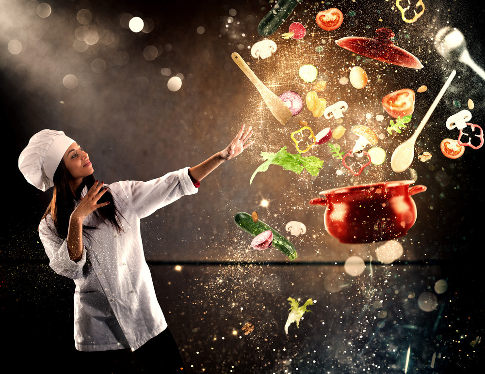 female chef gesturing towards a red levitating pot of vegetables