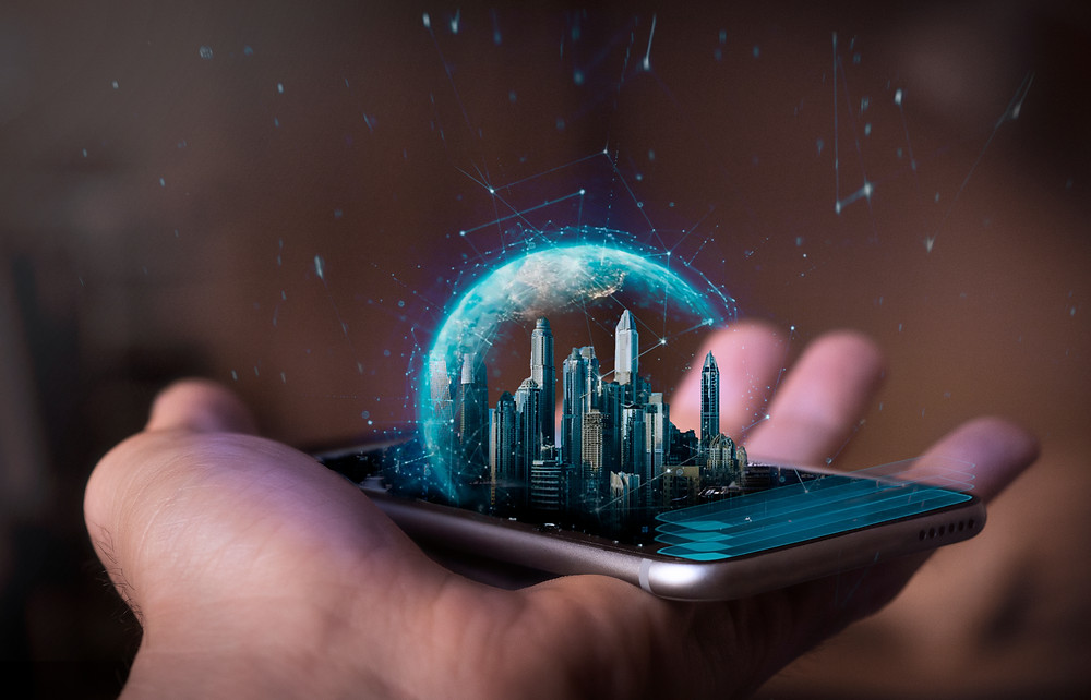 hand holding a futuristic phone with a holographic image of a futuristic city