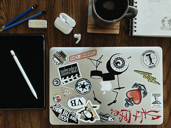 Flat layout of coffee, laptop, pencil, and airpod case