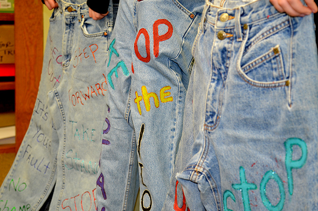 Two victims of sexual assault hold up decorated jeans at Audrain County Crisis Intervention Services in Mexico, Missouri on Tuesday, April 5, 2016. The jeans have messages raising awareness of sexual assault, and the jeans will be displayed as stuffed, 3-D figures in the month of April.