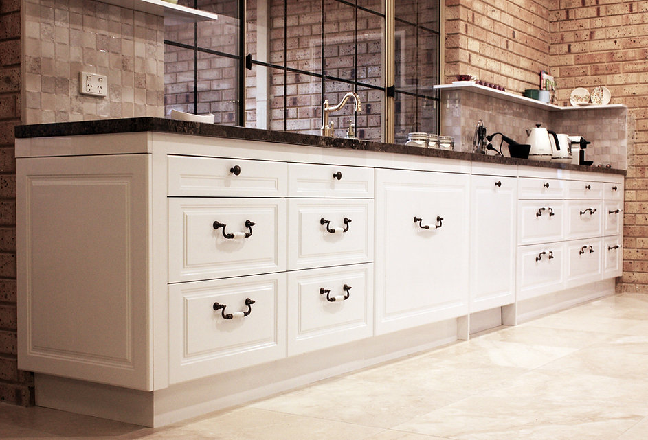 Traditional kitchen design with routed raised faced doors in white colour and antique brass handles and knobs.