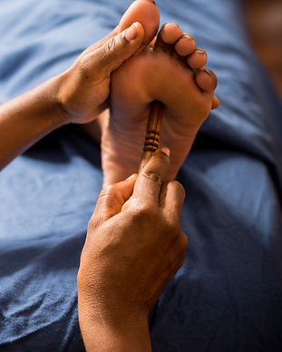 Massage therapist performing foot massag