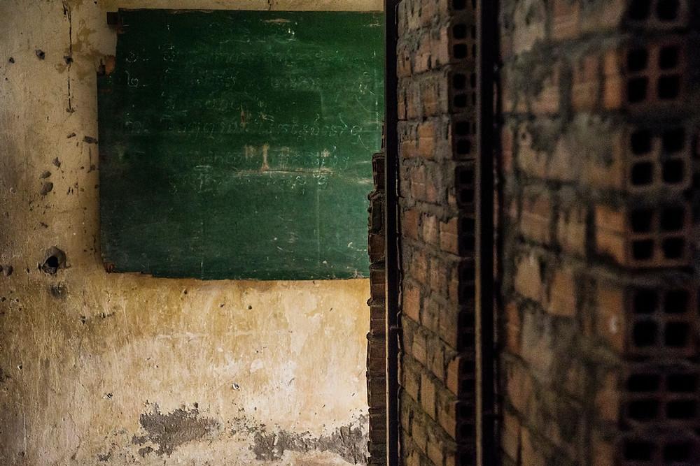 Le tableau noir des élèves devint le planning des tortionnaires de la prison. les murs de briques a droite sont les cellules ou bon nombres de prisonniers on subit des tortures atroces! (Sylvain Freulon©)