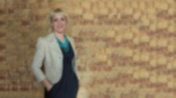 Kirsten Goodwin (Career Coach, Executive Coach, expert in Career Coaching) standing in front of a brick wall, smiling)