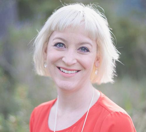 Kirsten Goodwin (Executive Coach, Career Coach) smiling at the camera in a orange top