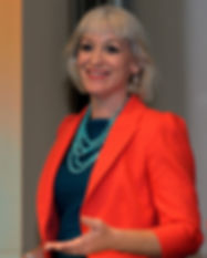 Kirsten Goodwin (Career Coach, expert in Career Coaching) speaking at an event in an orange jacket and turquoise necklace)
