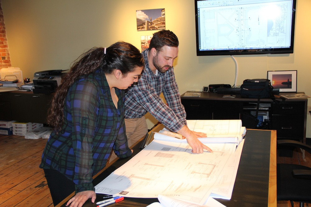 Project Manager, Eric Lafayette, goes over drawings with Intern, Meredith Hansen