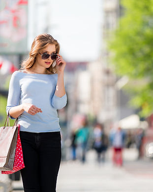 happy-young-woman-with-shopping-bags-wal