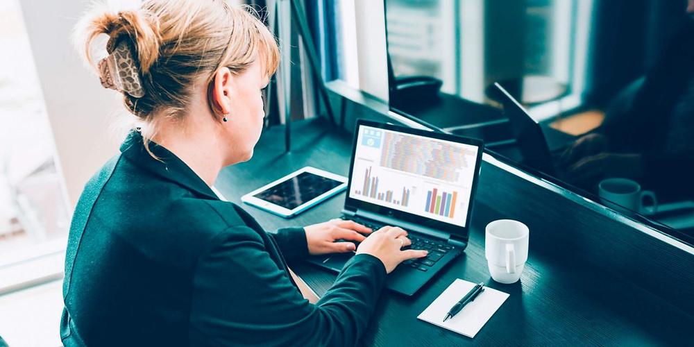 Mulher digitando no Laptop e visualizando graficos de melhoria gerencial de operações externas