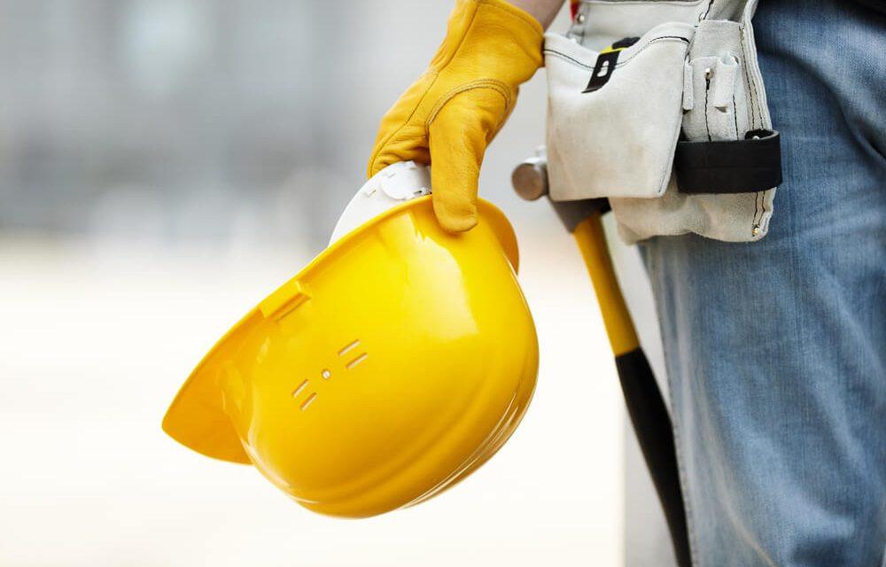 operario de construção civil com capacete amarelo pronto para fazer apontamento eletronico