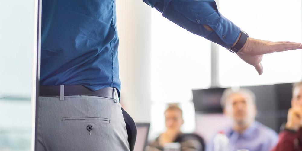 profissional gerenciando equipe em sala e explianco a função do apontamento eletronico para a equipe externa