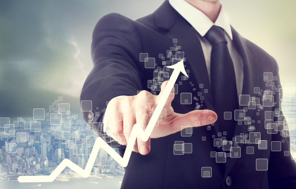 executivo de terno, apontando crescimento da empresa, com grafico simova subindo